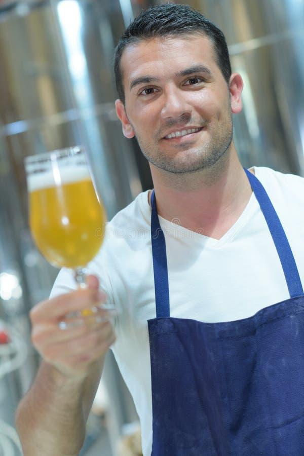 Piwowar trzyma szklanego pół kwarty piwny zdjęcie royalty free