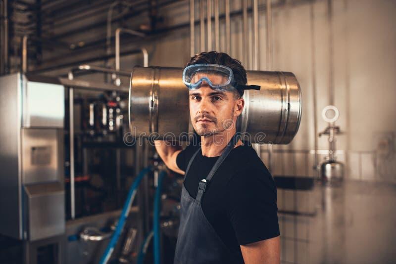 Piwowar z baryłką przy browar fabryką obrazy royalty free