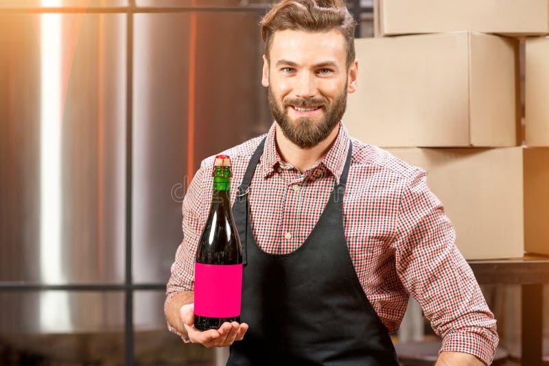 Piwowar z butelką przy produkcją fotografia stock