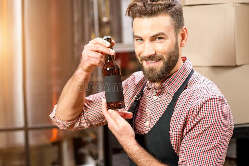 Piwowar z butelką przy produkcją obrazy royalty free