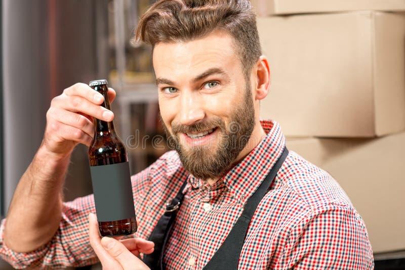 Piwowar z butelką przy produkcją zdjęcia royalty free