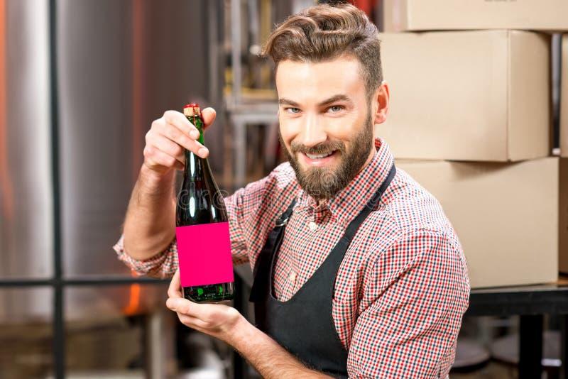Piwowar z butelką przy produkcją fotografia royalty free