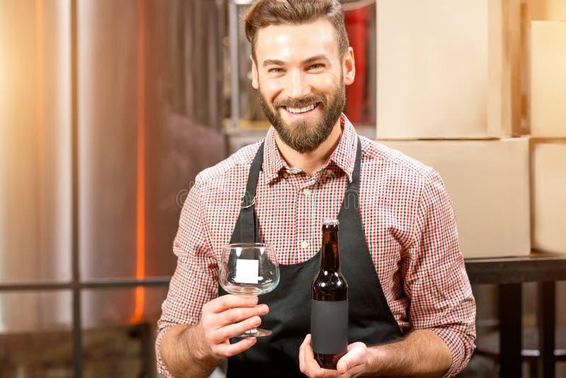 Piwowar z butelką przy produkcją obraz stock