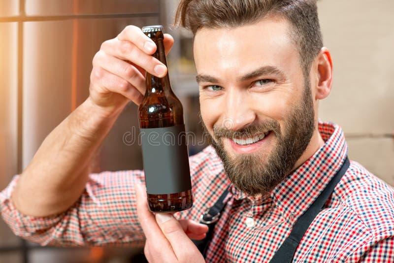 Piwowar z butelką przy produkcją obraz royalty free