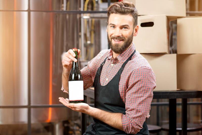 Piwowar z butelką przy produkcją zdjęcia stock