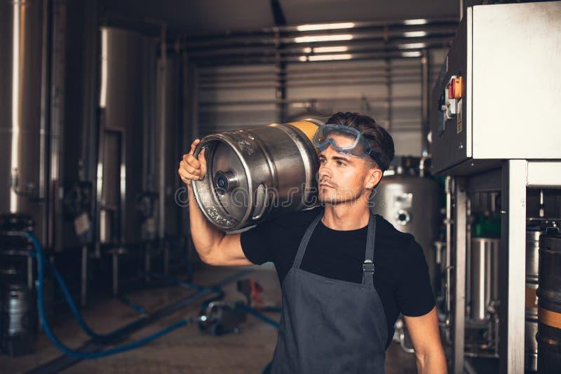 Piwowar z wielkim metalu zbiornikiem przy browar fabryką obrazy stock