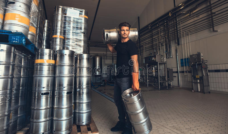 Piwowara przewożenia baryłka przy browar fabryką zdjęcia royalty free