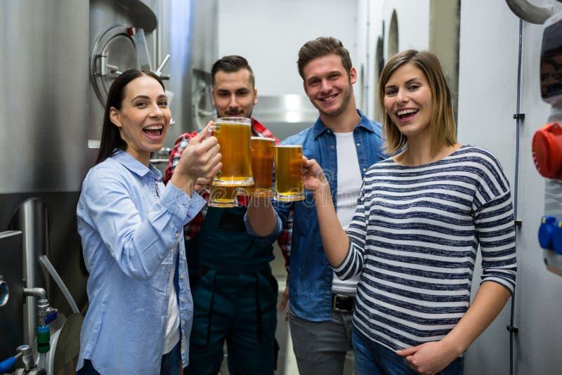 Piwowarowie wznosi toast piwa przy browarem zdjęcie royalty free