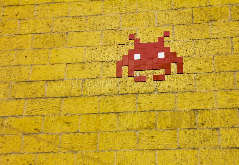 Pixel art of an alien on a yellow brick wall. A pixel art of an alien on a yellow brick wall royalty free stock photos