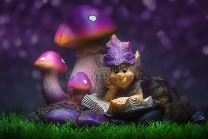 Pixie in violet. Pixie figure reading a book under mushrooms