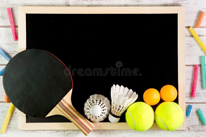 Pizarra, bola del volante, de ping-pong y pelota de tenis en blanco encendido foto de archivo