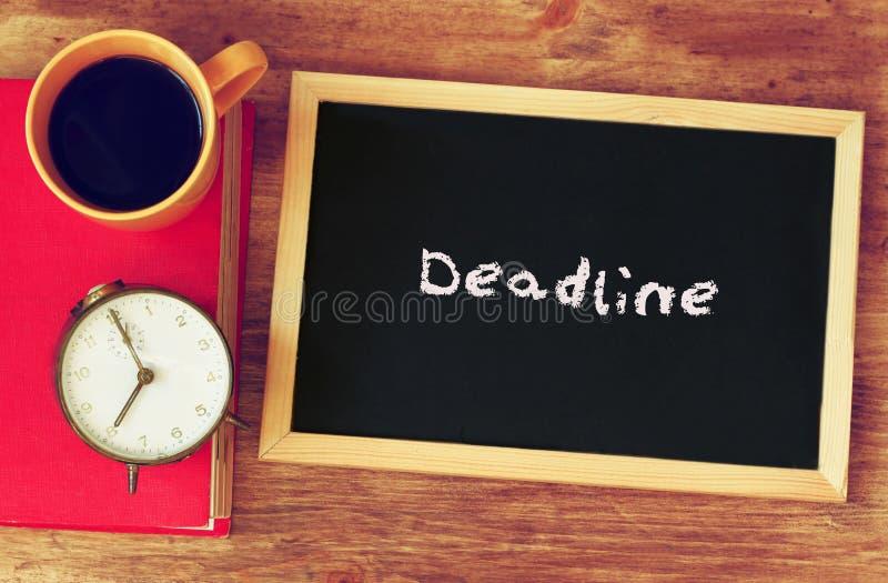 Pizarra con el plazo de la palabra escrito en la taza él, del reloj y de café sobre el tablero de madera imagenes de archivo