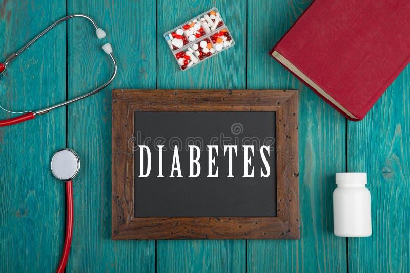 Pizarra con el texto y x22; Diabetes& x22; , estetoscopio, píldoras y libro en fondo de madera azul foto de archivo