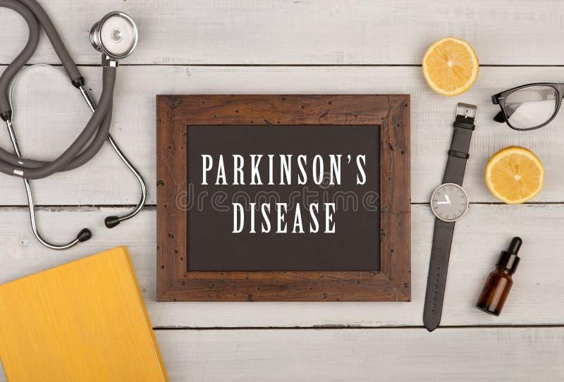 pizarra con el texto y x22; Parkinson& x27; disease& x22 de s; , libro, estetoscopio y reloj fotos de archivo libres de regalías