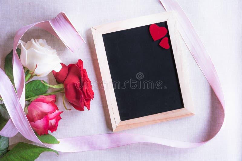 Pizarra con los corazones y las rosas rojos imagenes de archivo