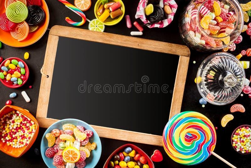 Pizarra de la escuela rodeada por el caramelo colorido imágenes de archivo libres de regalías