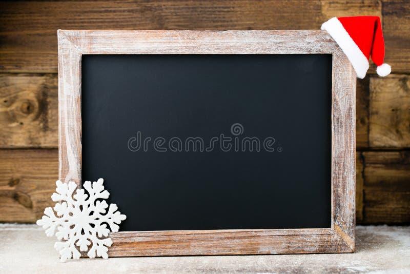 Pizarra de la Navidad con la decoración Sombrero de Papá Noel, estrellas, de madera imagenes de archivo