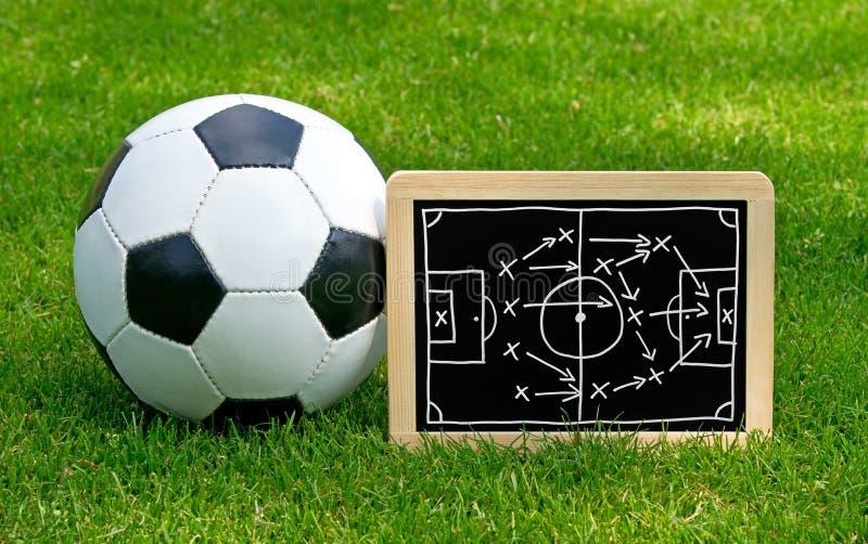 Pizarra de las táctica del fútbol con la bola de cuero fotos de archivo