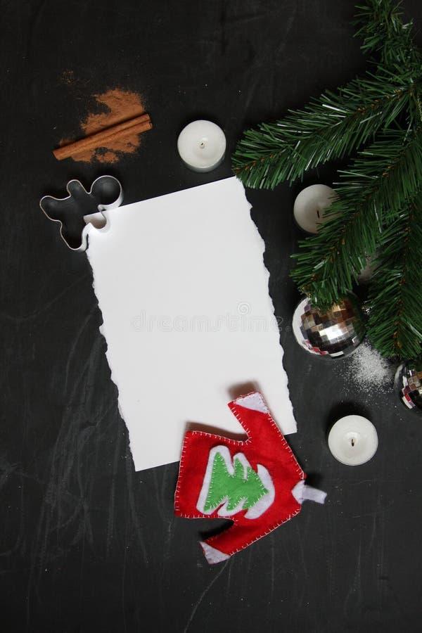 Pizarra del fondo con símbolos de la Feliz Navidad y del Año Nuevo: árbol imperecedero, canela, velas, trozo de papel blanco luga fotografía de archivo libre de regalías