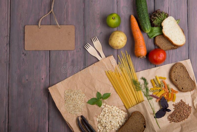 Pizarra en blanco, bolsas ecológicas con productos ricos en carbohidratos complejos: cereales, pan, pasta y verduras fotos de archivo