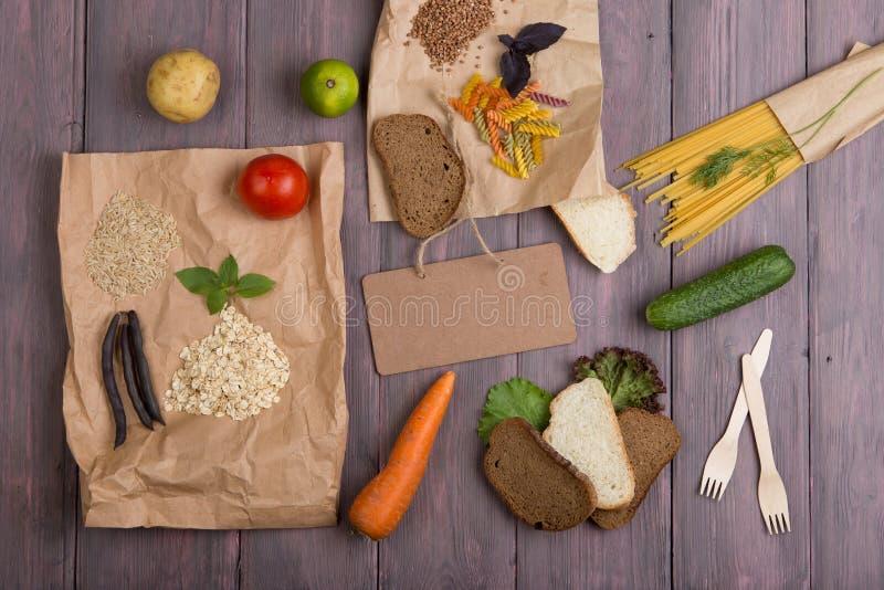 Pizarra en blanco, bolsas ecológicas con productos ricos en carbohidratos complejos: cereales, pan, pasta y verduras imagenes de archivo
