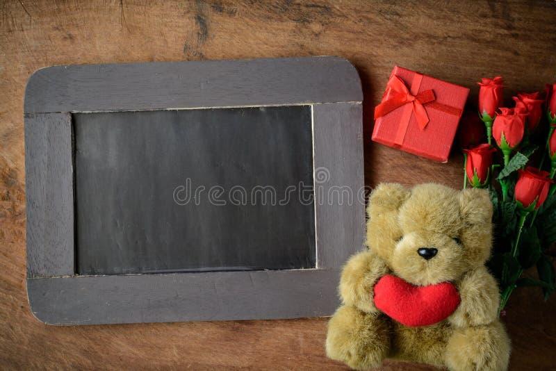 Pizarra en blanco con el oso y las flores de peluche imagen de archivo libre de regalías