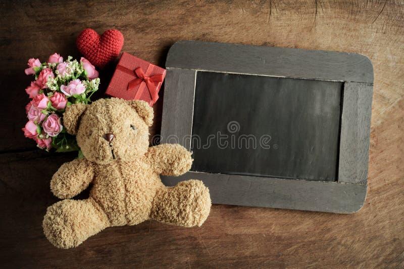 Pizarra en blanco con el oso y las flores de peluche fotos de archivo