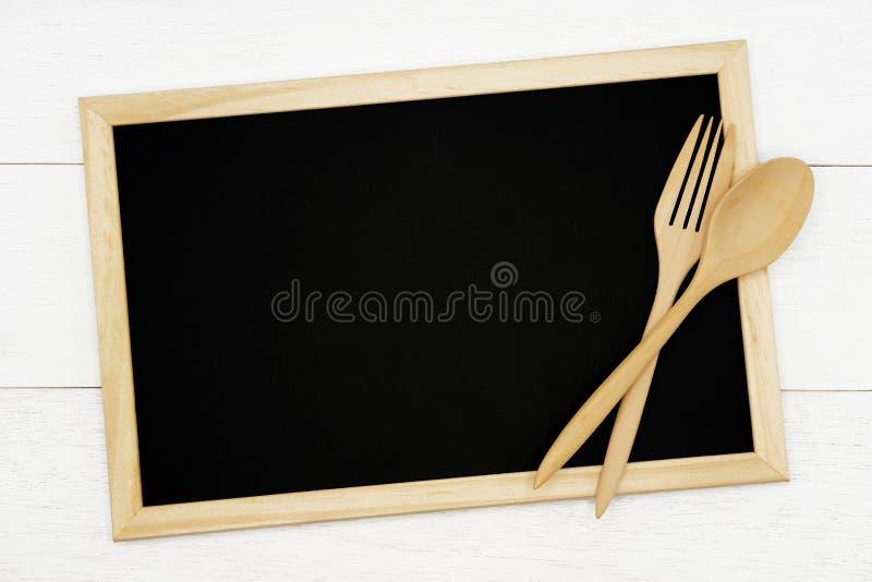 Pizarra en blanco con la cuchara de madera y bifurcación en el fondo de madera blanco del tablón fotografía de archivo libre de regalías