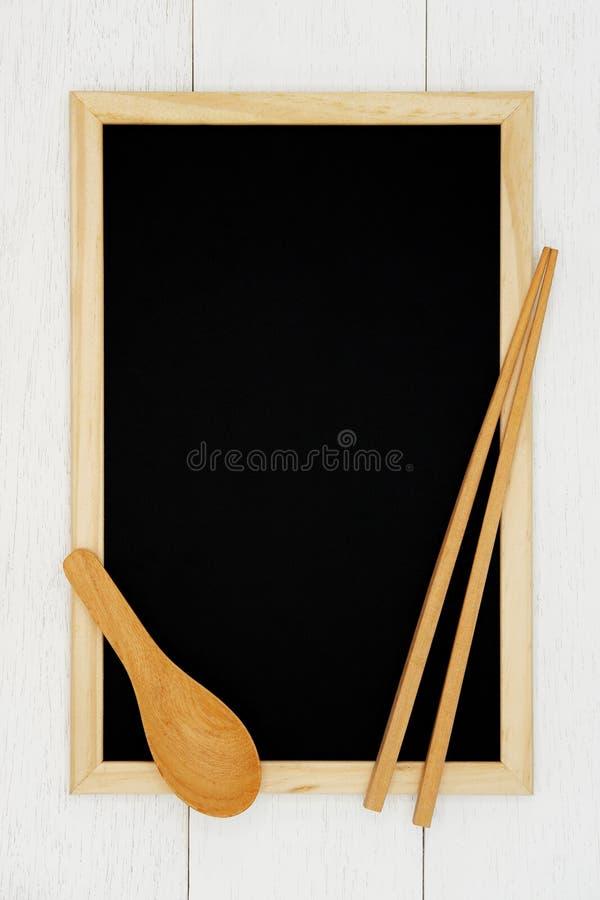 Pizarra en blanco con la cuchara y el palillo de madera en el fondo de madera blanco del tablón foto de archivo