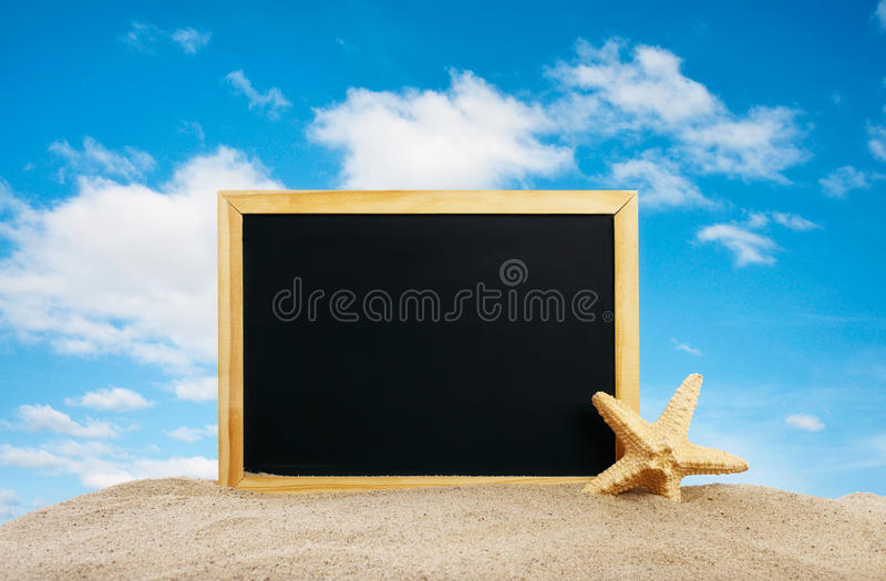 Pizarra en blanco con las estrellas de mar en la arena en la playa imágenes de archivo libres de regalías