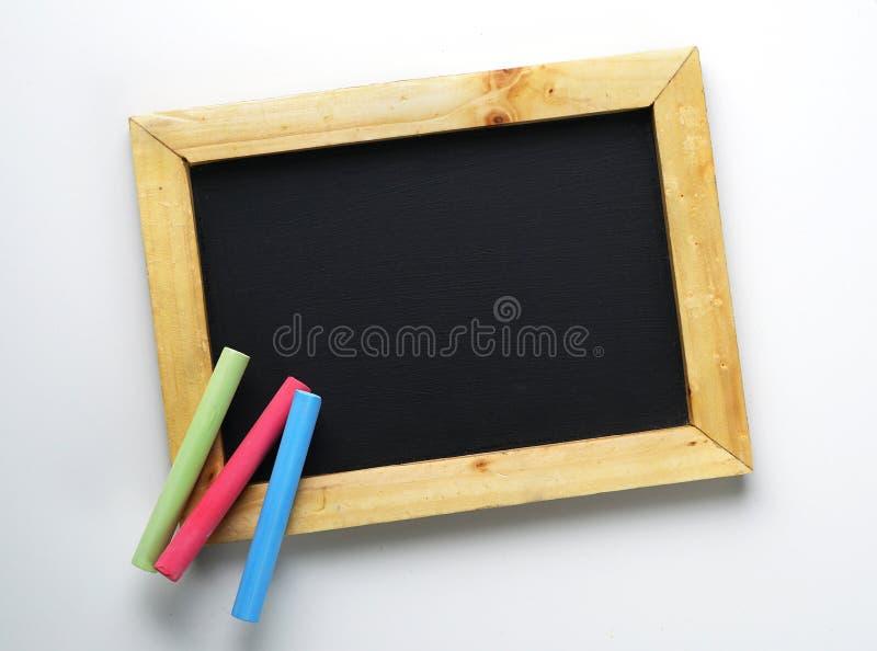 Pizarra en blanco del marco de madera con tiza colorida foto de archivo