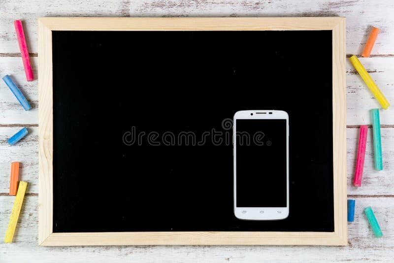 Pizarra en blanco y teléfono elegante en la tabla de madera Plantilla u falso foto de archivo