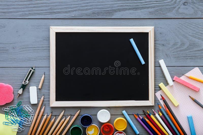 Pizarra en el escritorio oscuro gris con los lápices coloridos, pinturas, otras fuentes de escuela para el schoolwork, de nuevo a foto de archivo