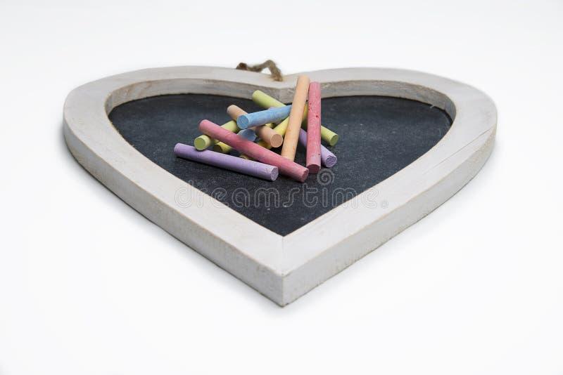 Pizarra en forma de corazón aislada con tiza coloreada imagenes de archivo