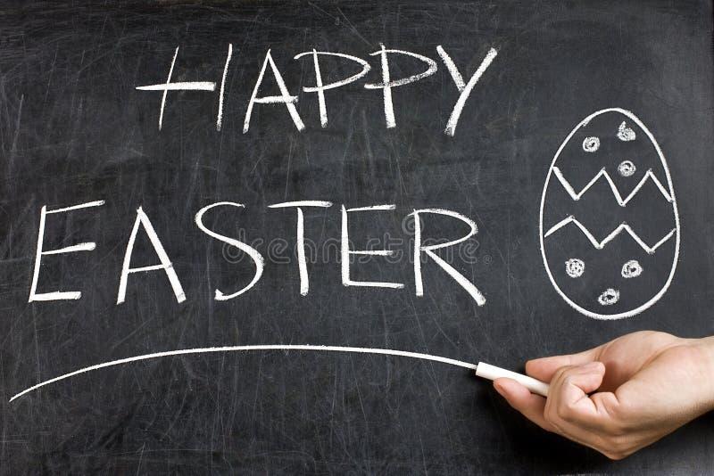 Pizarra feliz del huevo de la mano de Pascua fotos de archivo