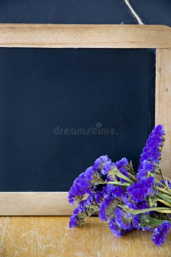 Pizarra negra con las flores fotos de archivo libres de regalías