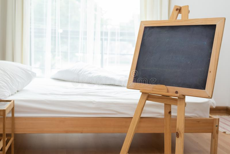 Pizarra negra en soporte del caballete en dormitorio con el fondo suave blanco de la cama Concepto del interior y de la decoraci? foto de archivo libre de regalías