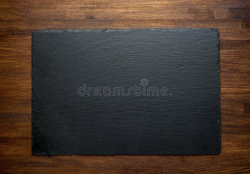 Pizarra sobre viejo fondo de madera fotografía de archivo libre de regalías