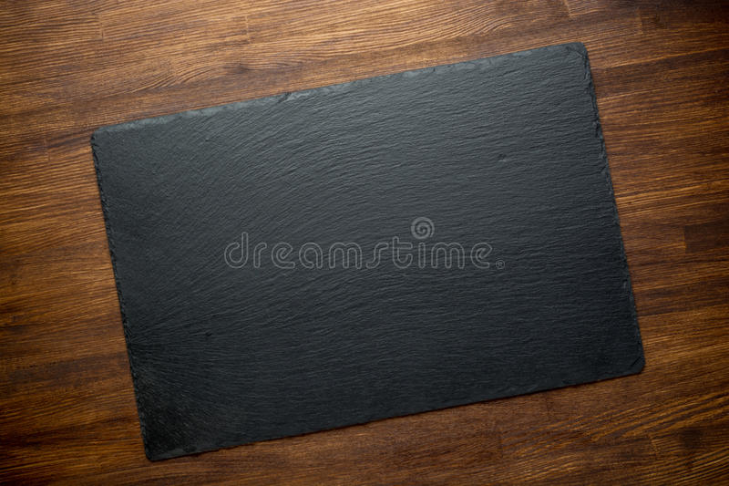 Pizarra sobre viejo fondo de madera fotos de archivo libres de regalías