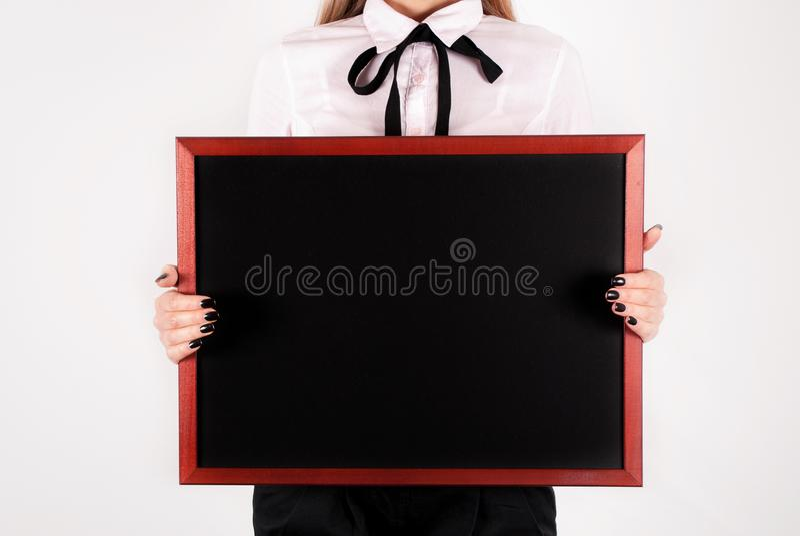 Pizarra vacía en manos de la muchacha y del espacio jovenes de la elegancia para el texto a bordo foto de archivo libre de regalías
