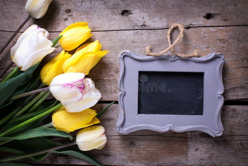 Pizarra vacía y tulipanes amarillos y blancos de la primavera en vintage fotos de archivo