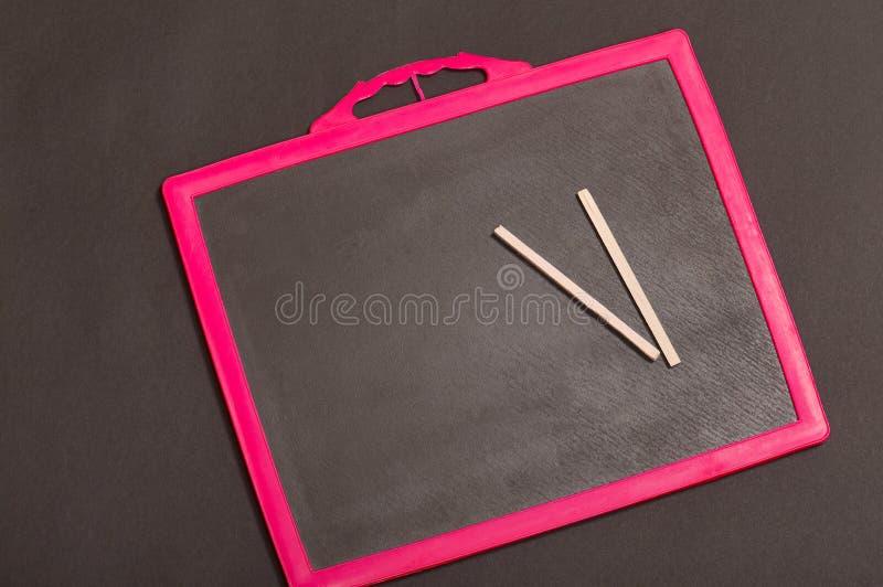 Pizarra y lápiz de la escuela en él imagenes de archivo
