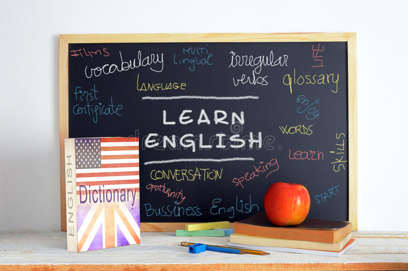 Pizarra y material de la escuela en una clase de inglés foto de archivo