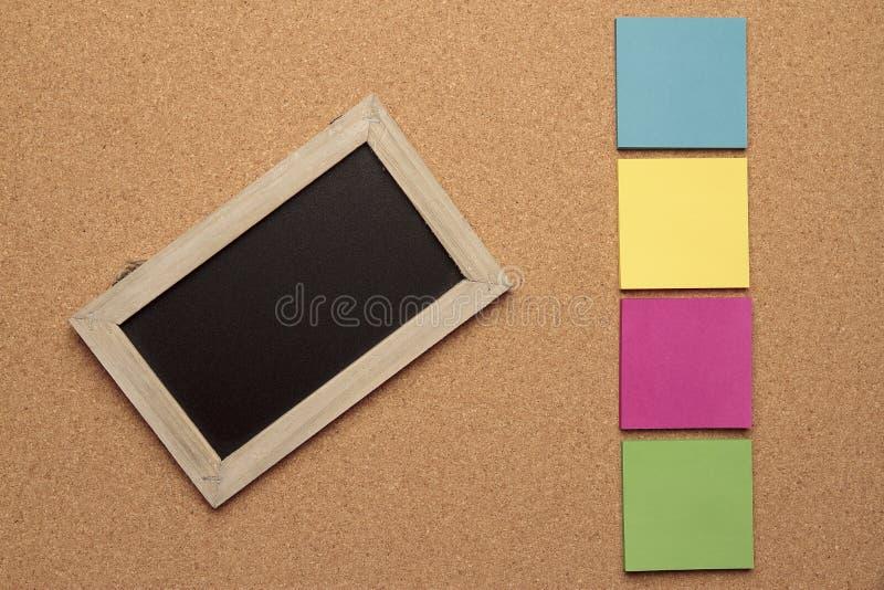 Pizarra y notas coloreadas fotografía de archivo libre de regalías