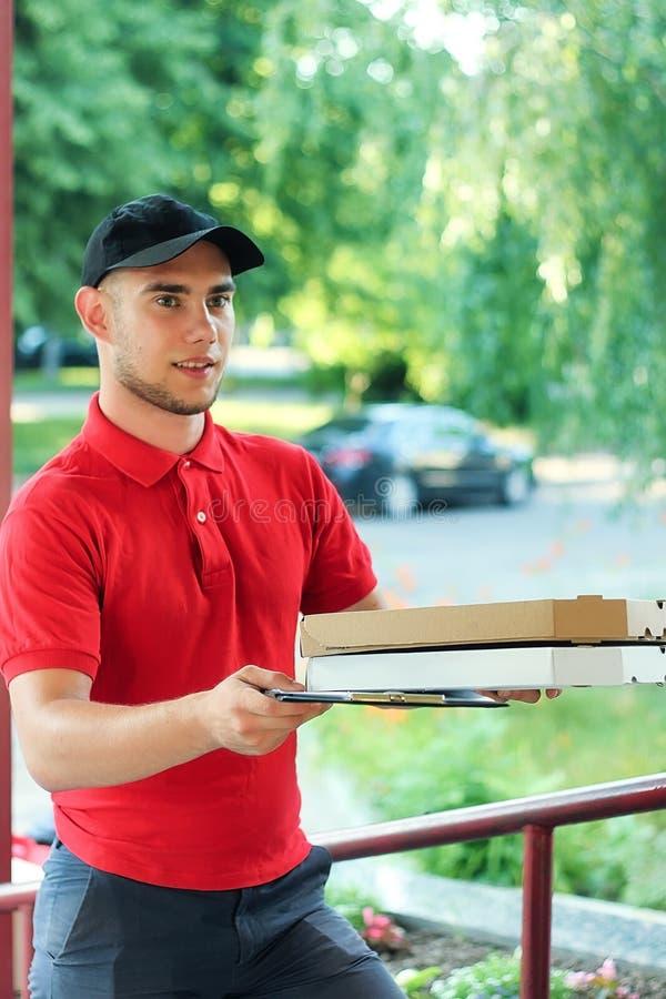 Pizzaåterförsäljaren med pizzaaskar kommer med beställningen royaltyfri fotografi