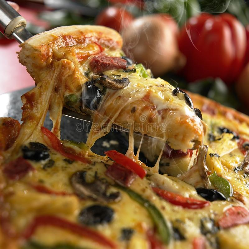 A pizza é levantada com espátula, colher da pizza Pizza, coberta com carne cortada, carne fumado, fatias da salsicha, cogumelos,  fotos de stock royalty free