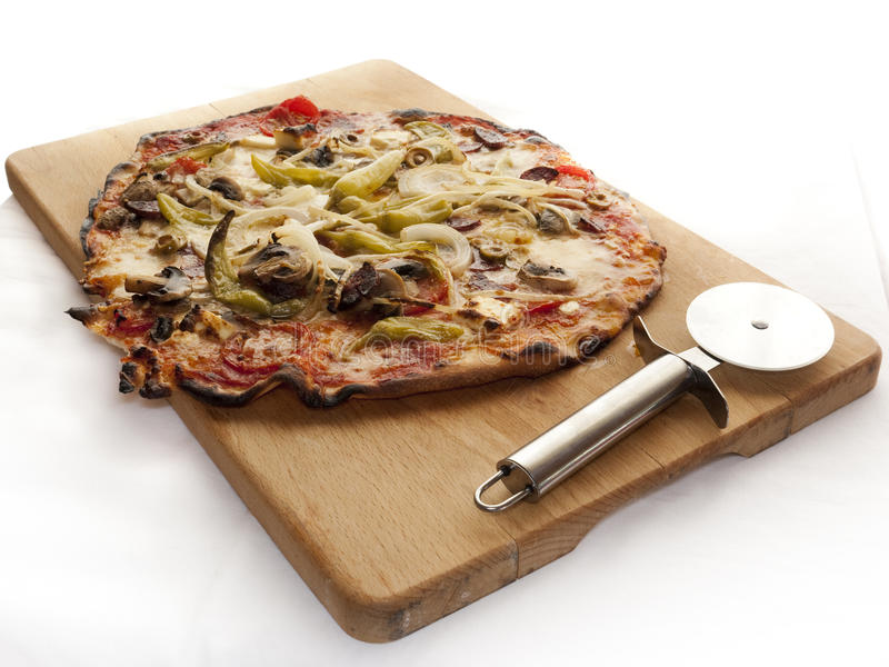 Pizza. Ready cooked pizza on a wooden board with a roll cutter besides it stock photography