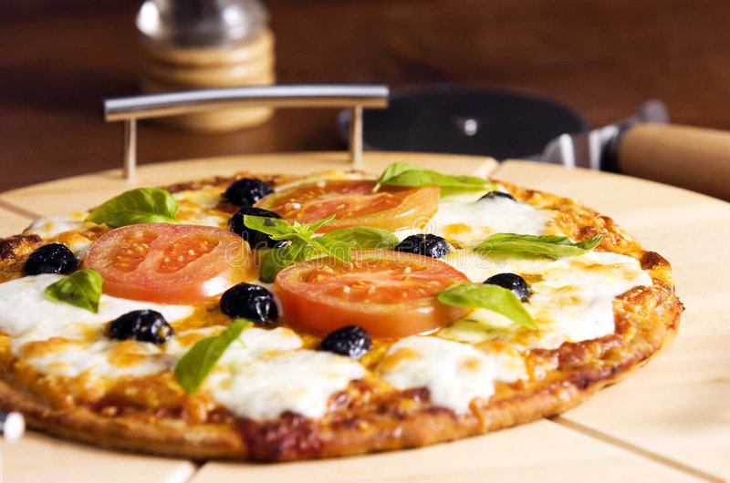 Pizza. With olives basil and tomato stock photos
