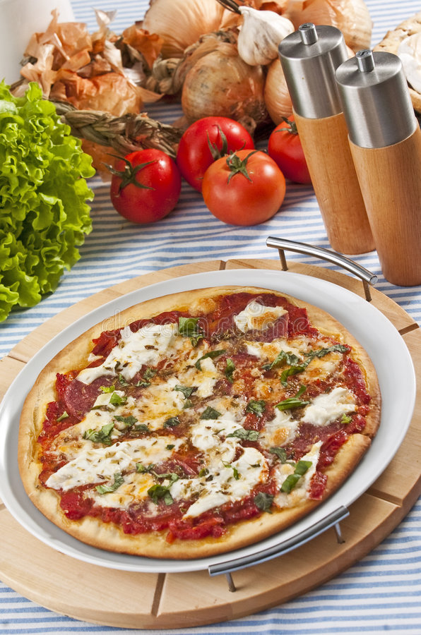 Pizza. Oven baked pizza served on wooden board stock photo