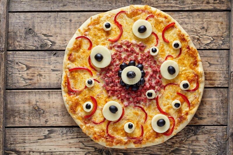 Pizza asustadiza del monstruo de la comida de Halloween con los ojos en la tabla de madera del vintage imágenes de archivo libres de regalías